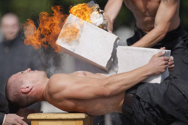 Dimanche 5 septembre, sur la base militaire de Minsk, un agent des forces spéciales du ministère de l'Intérieur de Biélorussie démontre sa force physique en se faisant briser une brique de ciment posée sur ses abdominaux avec une masse enflammée.