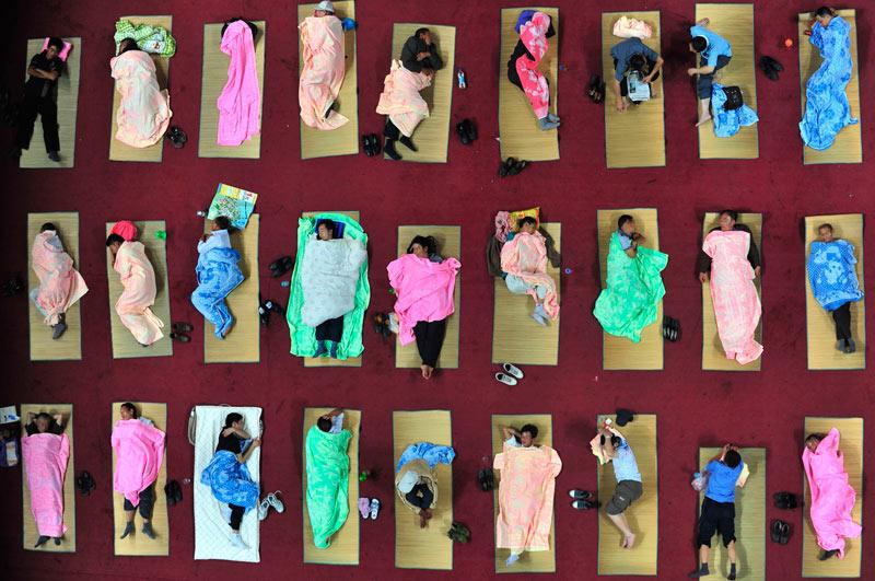 Ces parents d'élèves dorment sur des nattes installées sur le sol du gymnase du campus de l'université de Wuhan en Chine. Ils étaient au total environ 400 parents à accompagner leurs enfants, étudiants en première année, pour leur premier jour d'école.