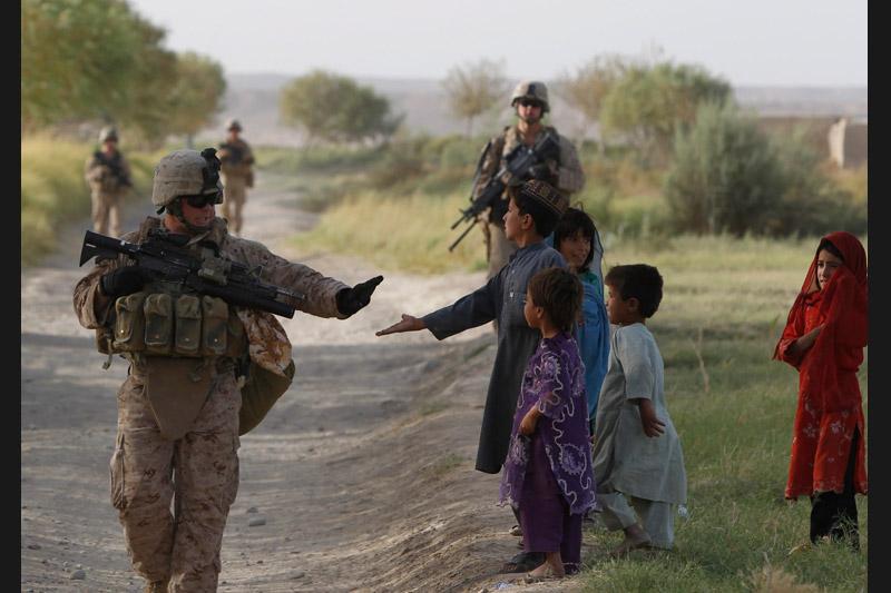 Mardi 7 septembre, un soldat américain salue des enfants lors d'une patrouille dans le village de Taghaz dans la province du Helmand au sud-est de l'Afghanistan.