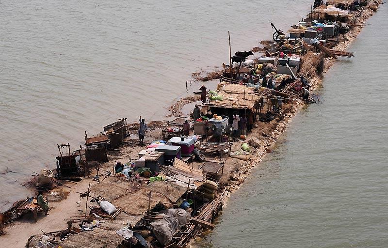 Mardi 14 septembre, à Khairpur Shah, six semaines après le début des inondations, ces Pakistanais se sont réfugiés sur une bande de terre et attendent la distribution des rations d'aide alimentaire.