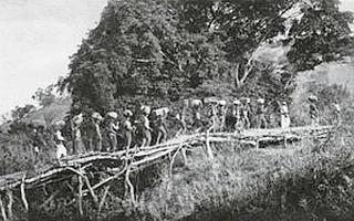 Sur le pont de la N'Gouni, route du Soueh. Au gré des haltes, près de 10.000 porteurs furent réquisitionnés pour acheminer les provisions, l'équipement et l'armement. Au total, 4.000 lots et 120 tonnes, réparties en charges de 30 kilos : c'est le poids que peut porter un homme sur une étape quotidienne…