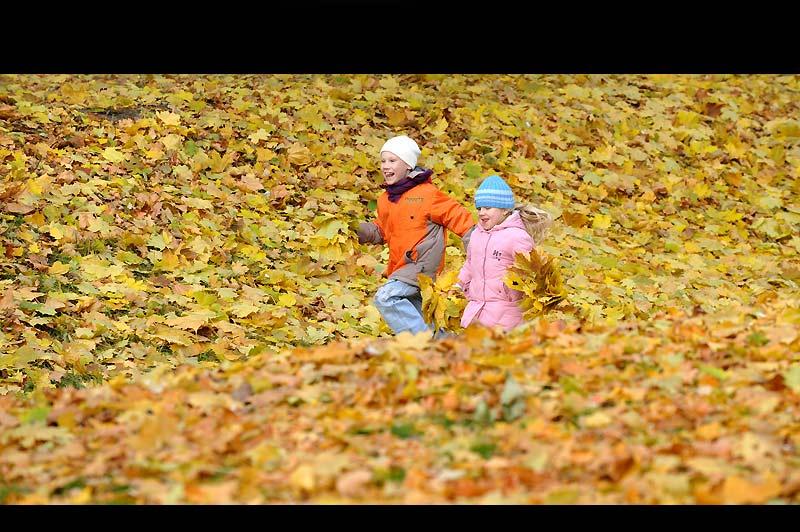Lundi 18 octobre, à Minsk, capitale de la République de Biélorussie, ces deux enfants courent avec plaisir dans une allée d'un parc recouvert d'un joli tapis de feuilles mortes fraîchement tombées.
