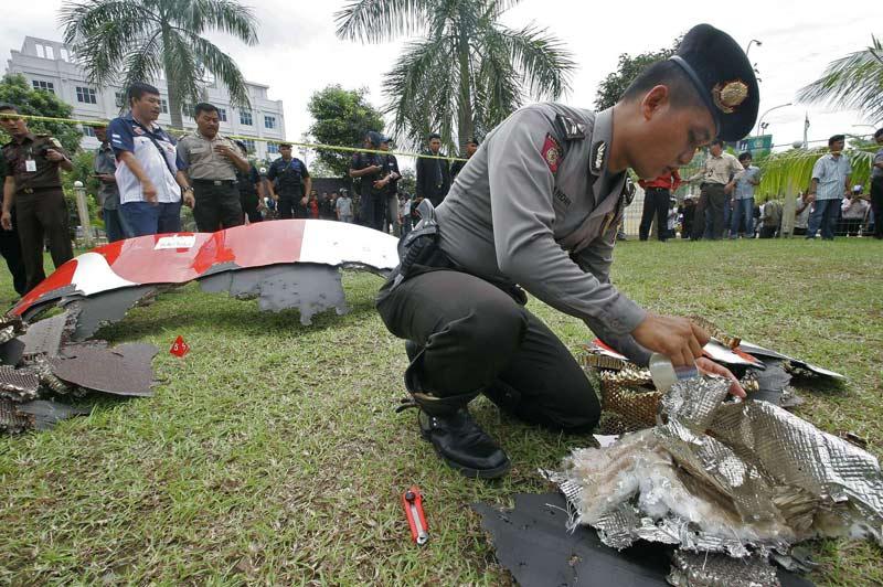 Jeudi 4 novembre, sur l'île indonésienne de Batam, un policier inspecte des débris tombés d'un Airbus A380 de la compagnie australienne Qantas, à la suite d'une avarie moteur. L'appareil a dû effectuer un atterrissage d'urgence à l'aéroport de Singapour.