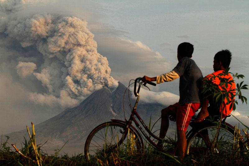 Ces deux enfants à vélo observent l'éruption du volcan Merapi, en Indonésie, mercredi 10 novembre. L'activité volcanique s'est calmée sur le mont, mais de fortes secousses sont toujours ressenties et le niveau d'alerte maximale reste maintenu.
