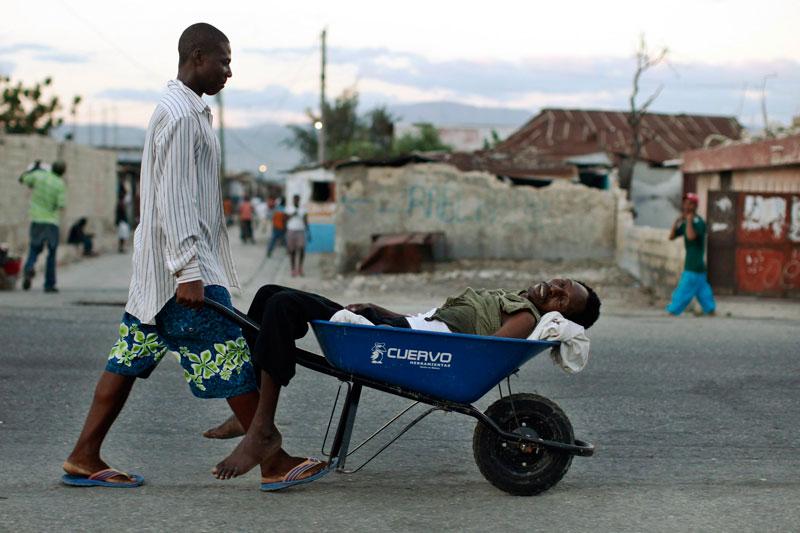 Cet Haïtien transporte un homme atteint du choléra vers un centre de soins de Port-au-Prince, le 19 novembre. À une semaine des élections législatives et présidentielle, le climat est extrêmement tendu dans un pays qui n'avait pas connu cette maladie depuis au moins un siècle.