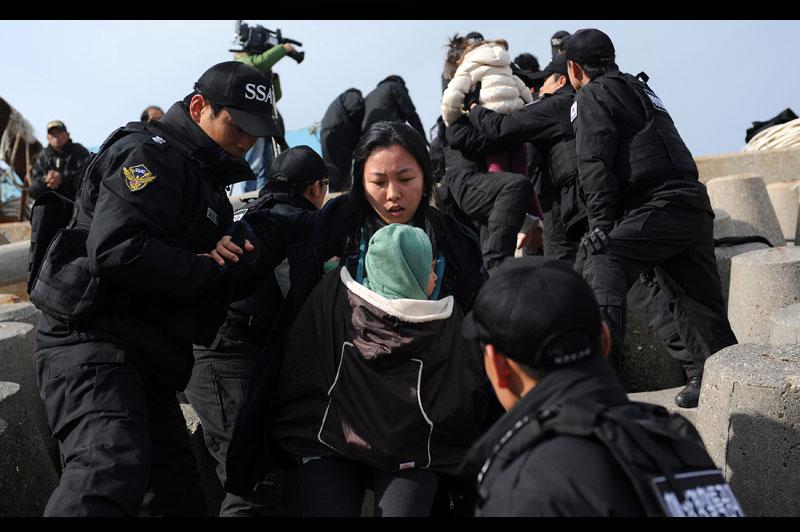 Mercredi 24 novembre, des garde-côtes sud-coréens évacuent les habitants de la petite île de Yeonpyeong, au lendemain du bombardement par la Corée du Nord. Encore terrifiés, nombre d'entre eux ont juré de ne jamais regagner leurs maisons.