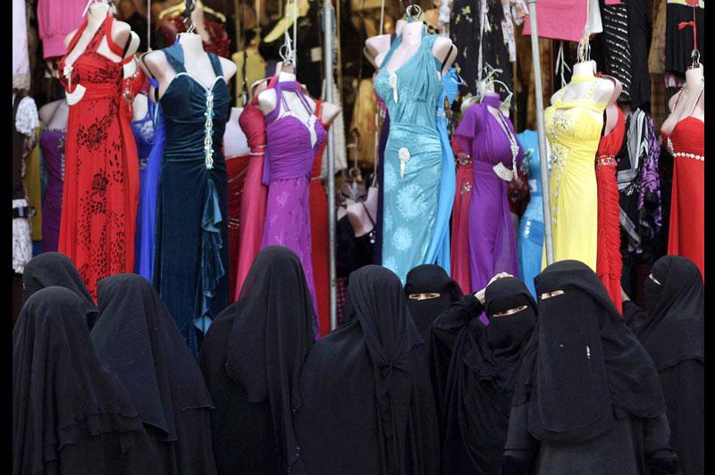 Dans les rues de Sanaa, la capitale du Yémen, ces femmes intégralement voilées observent la vitrine d'un magasin de robes, lundi 22 novembre.