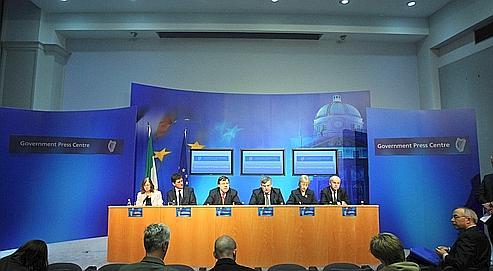 Le premier ministre irlandais Brian Cowen (au centre) parle aux médias après le feu vert définitif à un plan de renflouement de 85milliards d'euros pour Dublin.
