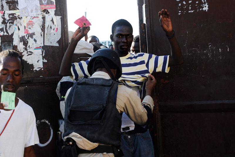 Dimanche 28 novembre, devant l'entrée d'un des bureaux de vote de Port-au-Prince, en Haïti, les fouilles sont de rigueur. Les élections se sont achevées dans la confusion : douze des dix-huit candidats au scrutin présidentiel ont réclamé son annulation en faisant état de fraudes massives.