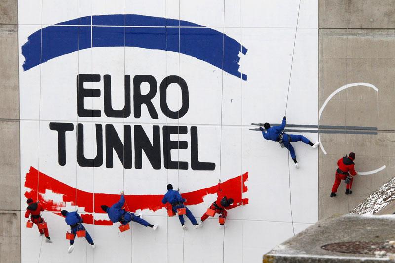 Mardi 1er décembre, pour célébrer le 20ème anniversaire de la première galerie creusée sous la mer entre la France et l'Angleterre, des ouvriers peignent un logo géant à l'entrée du tunnel, à Coquelles. La construction du tunnel sous la manche, qui a été inauguré en 1994, aura duré six ans.