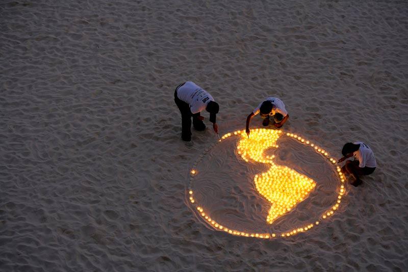 Alors que se tient en ce moment au Mexique le sommet international sur la lutte contre le réchauffement climatique, des membres du WWF ont déposé, lundi 6 décembre, sur la plage de Cancun, des bougies représentant la terre.
