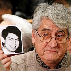Bernard Alexandre Chanfreau brandit une photo de son frère Alphonse à l'ouverture du procès.