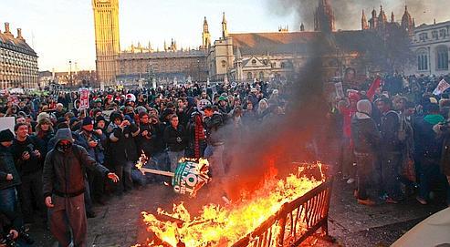 Des manifestants ont allumé un feu, jeudi, place du Parlement, à Londres.