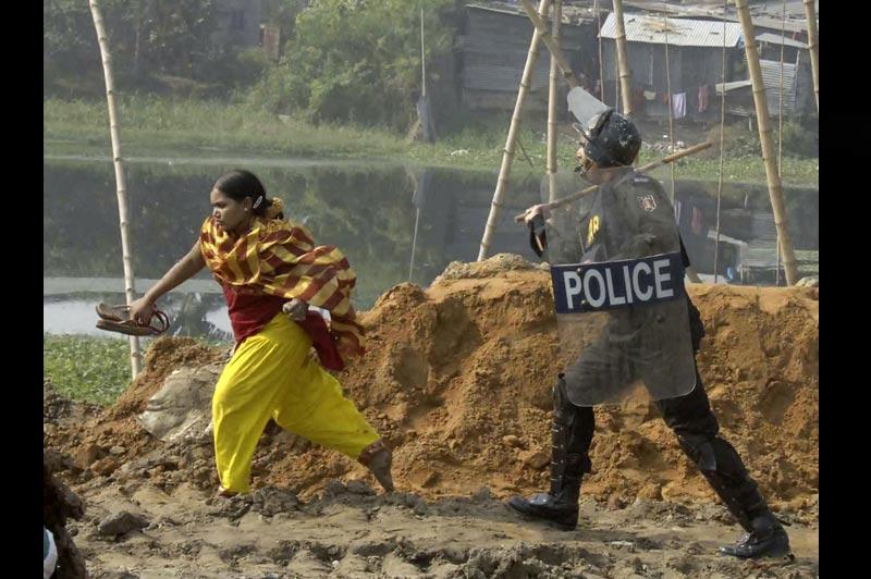 Lundi 13 décembre, à Dhaka, au Bangladesh, un policier disperse une ouvrière d'une usine de vêtements qui manifestait avec d'autres pour obtenir une augmentation de salaire.