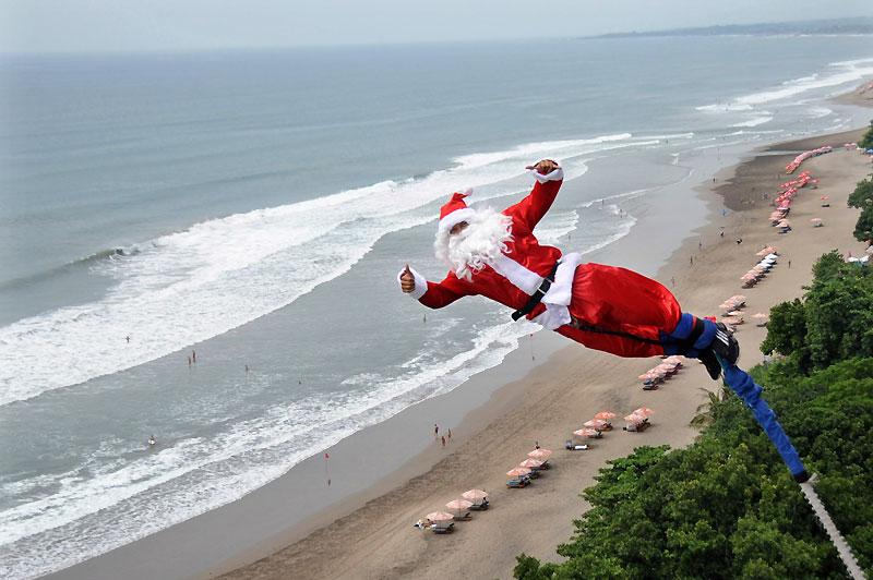 Jeudi 16 décembre, ce père Noël fait un saut à l'élastique au-dessus d'une plage à Kuta, à Bali.