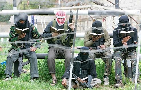 Des membres du Fatah al-Islam, mouvement inspiré d'al-Qaida, lisent le Coran dans le campde Nahr al-Barid, au Liban, en mars 2007.
