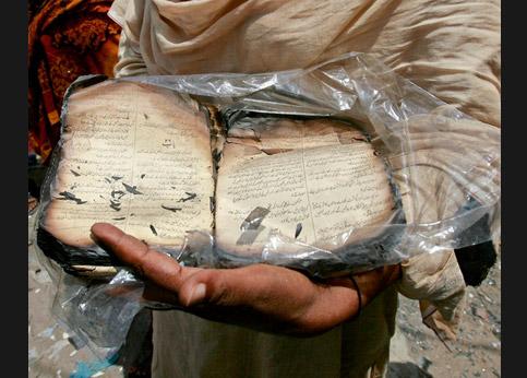 <strong>Attester.</strong> Dans la région du Pendjab au Pakistan, une chrétienne montre une Bible brûlée au cours d'un attentat islamiste.