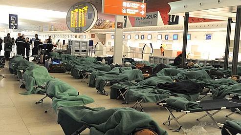 Des passagers dorment sur des lits de camps dans la nuit de jeudi à vendredi, à l'aéroport de Roissy-Charles-de-Gaulle.