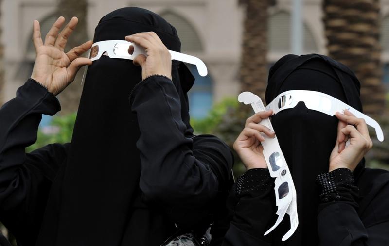 Deux femmes voilées observent l'éclipse en Arabie Saoudite à travers des lunettes spéciales qui permettent de protéger la rétine des rayons solaires.
