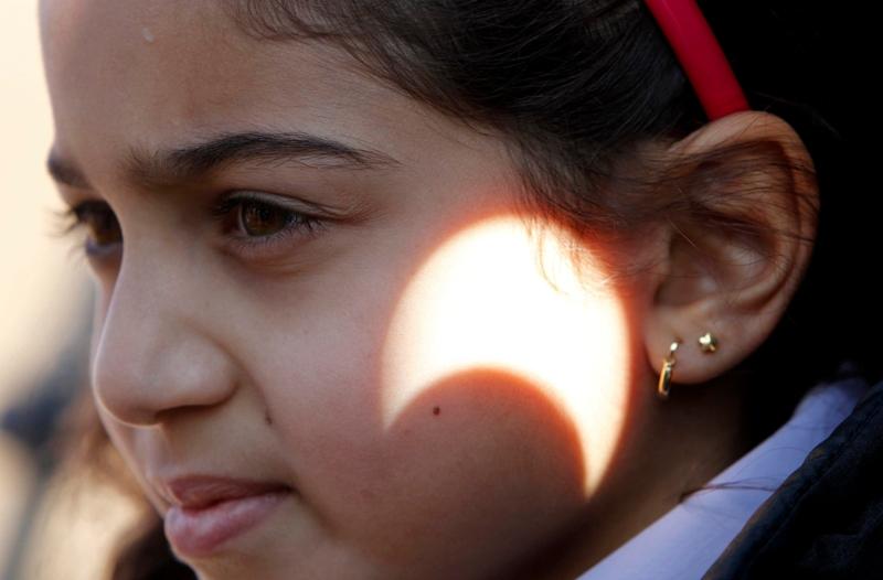 Une petite fille pose à Amman en Jordanie alors que l'éclipse se projette sur sa joue. Une autre manière de profiter de ce spectacle naturel.