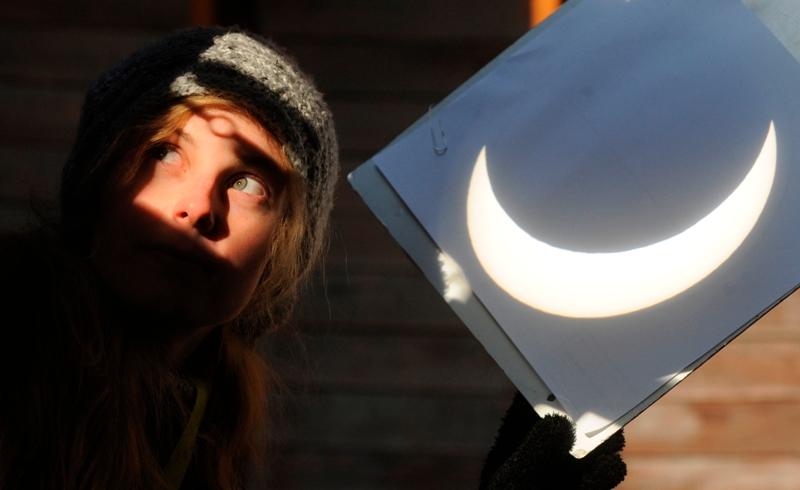 Une jeune fille de l'observatoire de Prague utilise une feuille de papier comme écran pour montrer l'éclipse aux curieux ne disposant pas de lunettes adaptées à une observation directe.
