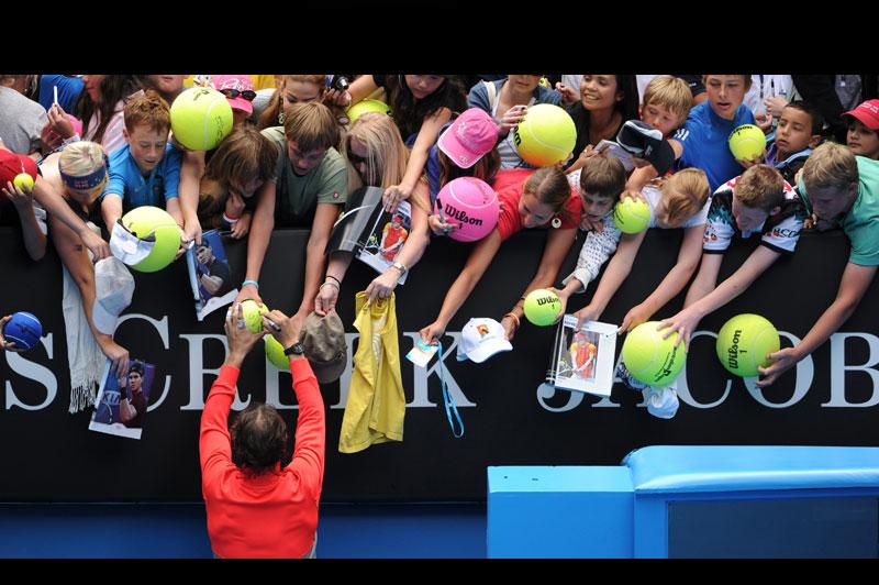 Rafael Nadal signe des autographes après sa victoire expéditive lors du premier tour de l'Open d'Australie, mardi 18 janvier, à Melbourne. Le numéro un mondial a bénéficié de la blessure au genou du brésilien Marcos Daniel pour s'imposer en 47 minutes, en moins de deux sets 6-0, 5-0.