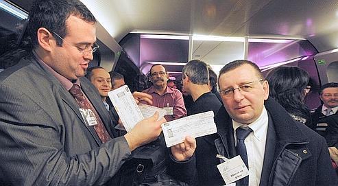 Des usagers quotidien de la ligne Angers-Le Mans-Paris posent avec leurs billets alors qu'ils arborent un badge «abonné en grève», le 18 janvier 2011 dans le train reliant le mans à paris.