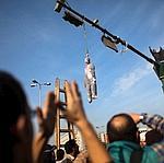Des manifestants devant une effigie du président Moubarak suspendue à un feu de signalisation, place Tahrir, au Caire.