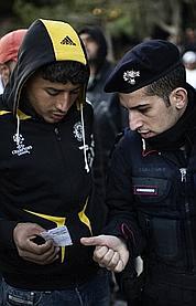 Un migrant tunisien se renseigne auprès d'un policier italien dans les rues de Lampedusa.