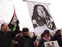 Des manifestants brandissent une banderole avec Kadhafi grimé en Hitler devant la Maison-Blanche, à Washington.