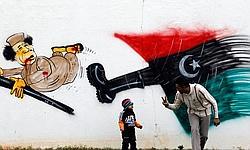 Un père joue avec son enfant devant un dessin de Kadhafi malmené par la révolte populaire.