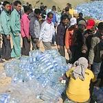 Des réfugiés font la queue jeudi pour obtenir de l'eau.