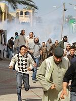 Des manifestants anti-Kadhafi fuient les forces de l'ordre, à Tripoli.