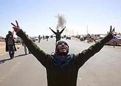 Un rebelle fait le signe de la victoire, défiant le pilote de l'armée libyenne qui vient de larguer une bombe à proximité de Ras Lanouf.