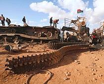 Des Libyens inspectent les blindés détruits par la coalition.