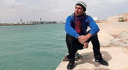 Bilal Zairi sur le port de Zarzis. Par deux fois, le jeune Tunisien a déjà tenté de gagner l'île italienne de Lampedusa. Photos : Cyrile Biton et Giuseppe Carotenuto.