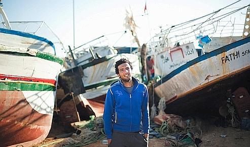 Sous le soleil de Lampedusa, Bilal contemple le cimetière des bateaux tunisiens saisis par les gardes-côtes italiens.