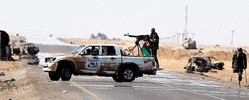 Des insurgés libyens protègent l'entrée dans la ville d'Ajdabiya jeudi.