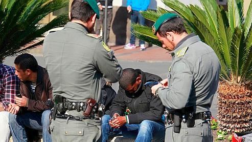 Des policiers italiens contr?lent des migrants, à Vintimille.