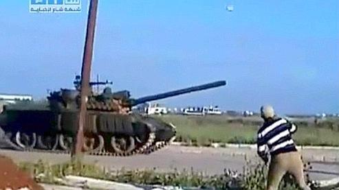 Sur cette image tirée d'une vidéo réalisée par un groupe syrien de défense des droits de l'homme, un homme lance un projectile sur un char, à Deraa.