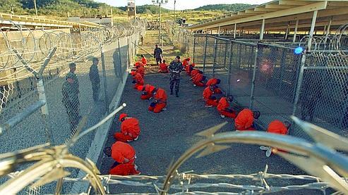 Des prisonniers de Guantanamo (en orange) sous le regard de la police militaire le 11 janvier 2002.