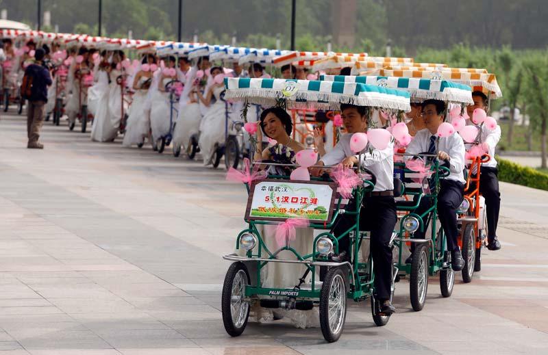 <b>À la chaîne</b>. C'est une journée porte-bonheur. Comme chaque année, le 1er mai est une date prisée pour de nombreux couples qui souhaitent se marier. À Wuhan, dans la province du Hubei, en Chine, les demandes étaient si importantes qu'une cérémonie de masse a été organisée, avec, en bonus pour les heureux mariés, un petit tour de carriole.