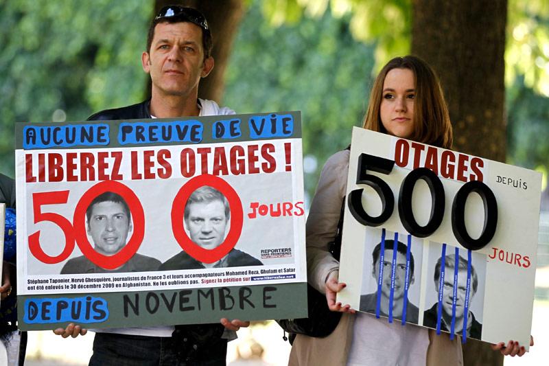 A Paris, des manifestants brandissent des portraits des journalistes français, Hervé Ghesquière et Stéphane Taponier, pour marquer le 500ème jour de leur captivité en Afghanistan