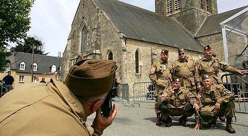 Un groupe de militaires se prennent en photo à Sainte-Mere-Eglise, en Normandie, l'une des premières communes de France libérées le 6 juin 1944.