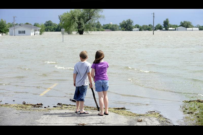 <b>En crue</b>. On en a tous rêvé. Enfin, loin du regard de leurs parents, ils peuvent mettre les pieds dans cette énorme flaque. Sur cette photo, prise mardi 21 juin, dans la région de Corning, dans le Missouri, le fleuve du même nom, en crue, n'en finit pas de provoquer de fulgurantes inondations. En débordant de ses digues, plus de 1000 hectares de terres agricoles ont été totalement envahies par les eaux et des centaines de personnes ont dû fuir leurs habitations. Selon les experts, la décrue devrait s'amorcer lentement ces prochains jours. Mais pour les sinistrés, le retour à la normale pourrait prendre plusieurs semaines.