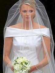 La princesse est vêtue, comme annoncé, d'une robe signée Armani, en soie duchesse blanc-cassé.