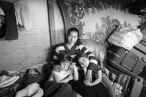 «Montreuil, France, mai 2010». ©Alain Keler / M.Y.O.P-2011. Une famille de Roms de Roumanie vient d'apprendre qu'ils devront quitter bientôt leur baraquement situé à proximité d'une entrée d'autoroute. Ils vivent au milieu de leurs bagages en attendant un départ lié à la recherche d'un nouvel endroit où ils pourront vivre.