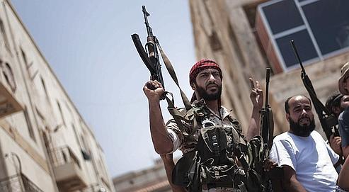 Des rebelles assistent aux funérailles d'un combattant à Benghazi, le 22 juillet.