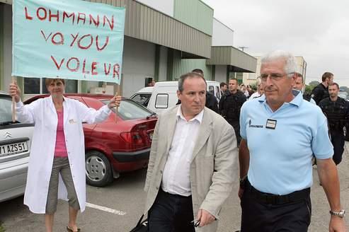 Un gendarme escorte le 29 juin 2011, le directeur de l'entreprise Sodimédical, Dominique Richard, à sa sortie de l'usine où il était retenu.