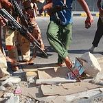 Des rebelles visent un portrait de Kadhafi, à Tripoli, le 22 août 2011.